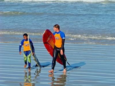 Adventure holidays are a great way to combine excitement with altruism - here, a male volunteer walks with a boy in a surf project in South Africa