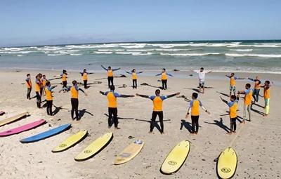 A volunteer teaching children how to surf