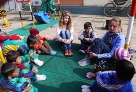 Two Care & Community volunteers in Nepal sit in a circle with local children, preparing to play an educational game.