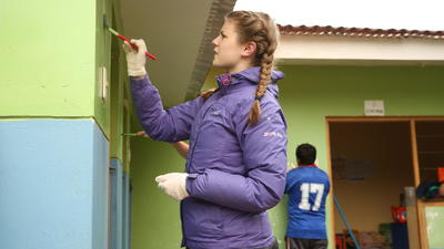 Projects Abroad Care and Community volunteer paints the wall of a local primary school
