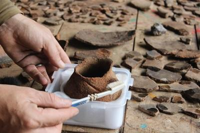 A Projects Abroad volunteer on the Inca project carefully cleans a ceramic in Peru