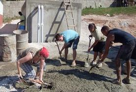 Building volunteers in Jamaica mix cement during the construction of a new house.