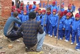 Local children in Nepal look on excitedly while volunteers help with building classrooms for a school damaged during the 2015 earthquake.
