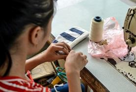 A local woman weaves textiles for the small business in Vietnam where our volunteers work.