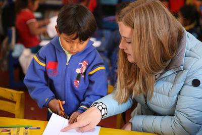Volunteering with children abroad allows you to support the work of local staff. Here, a Projects Abroad Care volunteer explains to young child how to cut using scissors