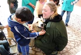A Canine Therapy volunteer works with a disabled child in Bolivia, helping him bond with his therapy dog.