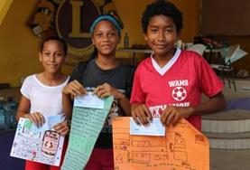 Local children in Belize show off posters they made for a project at one of our Care placements.