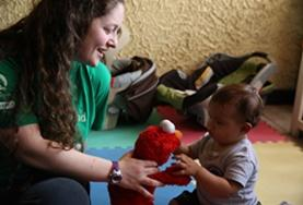 A volunteer plays with a child using a soft toy at our Care placement in Costa Rica.