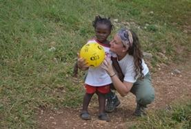 A volunteer plays a ball game with a young child at one of our childcare placements in Jamaica.