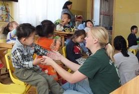 Childcare volunteers in Mongolia work one-on-one with young children, playing educational and fun games.