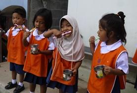 Local children learn how to brush their teeth correctly under the guidance of one of our childcare volunteers in Thailand.