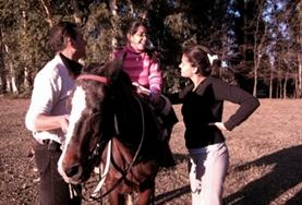 An Equine Therapy volunteer in Argentina speaks to a child before starting a treatment session with her therapy horse.