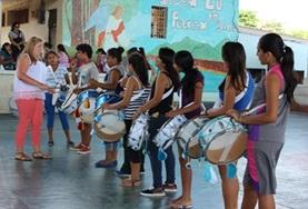 A Creative Arts volunteer working in Ecuador teaches a music lesson to local students using drums.