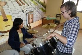 A Music volunteer teaches a local child how to play the drums during a music therapy session in Bolivia.