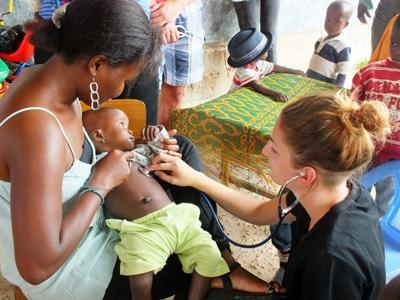 Elective volunteer examines a child on outreach programme