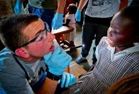 A medicine student volunteering in Kenya works at a community outreach to earn credit for his elective.
