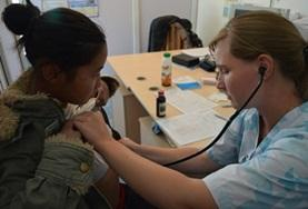 A volunteer working towards her Medicine Elective in Mongolia uses a stethoscope to check a local woman's heart rate.