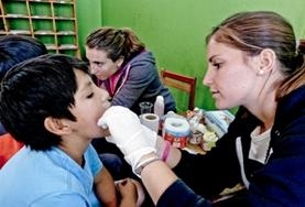 A Medicine Elective intern examines a child during a screening outreach in Peru, South America.