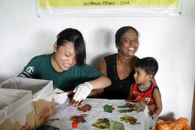 An Elective volunteer tests blood sugar levels in Sri Lanka