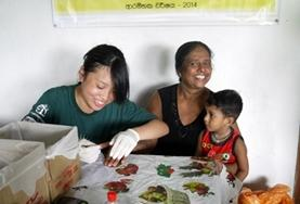 A Nursing Elective intern prepares to do a healthcare screening on a local child in Sri Lanka.