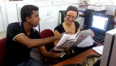 Member of staff and Journalism volunteer discuss articles
