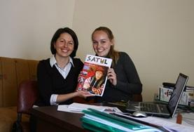 A local journalist and a Journalism intern in Romania hold the magazine they have been working on together.