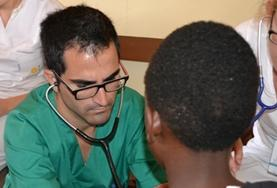 A Medicine volunteer checks a child's heart rate during a healthcare screening outreach in Kenya.