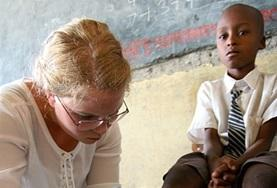 A Medicine intern helps with cleaning and dressing a child's wound at a healthcare outreach in Kenya.