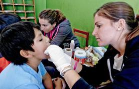 A Medicine intern examines a child during a medical outreach in Cusco, Peru.
