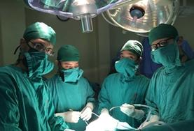 Medical interns in Vietnam observe a surgical procedure performed by a local doctor.
