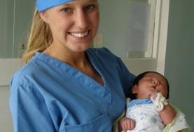A Midwifery intern volunteering in the maternity department of a Mongolian hospital holds a newborn baby.