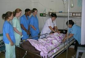 Nursing interns in Mongolia observe as local doctors insert an IV into a patient as part of her treatment.