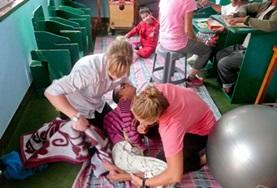 Two Physiotherapy volunteers work together to treat a disabled child during their internship in Nepal.