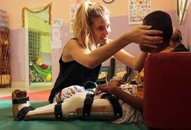 A Physiotherapy intern at our volunteer placement in the Philippines works with a disabled boy on improving his mobility.