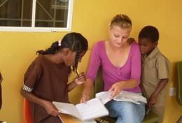 A qualified social worker does an activity with two local children at our volunteer placement in Jamaica.