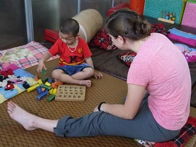 Physiotherapy volunteer Hannah Kimberly (USA) working with disabled child at Thuy An Rehabilitation Center