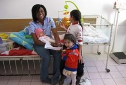 A professional massage therapist spends time with the children at her volunteer placement after a treatment session.