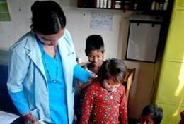 A qualified nurse volunteering in Nepal performs a healthcare screening check on local children in a hospital in Chitwan.