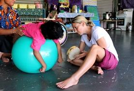 A qualified Occupational Therapist works on a mobility exercise with a disabled child at our volunteer placement in Samoa.