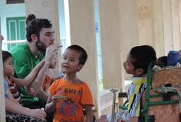 A qualified speech therapist volunteering in Vietnam works with local disabled children.