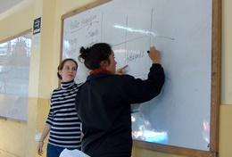 A qualified maths teacher volunteering in Peru works through a maths problem with a school student.