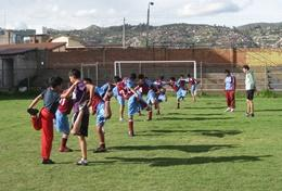 A professional physical education teacher leads school children through a stretching class at his volunteer placement in Peru.