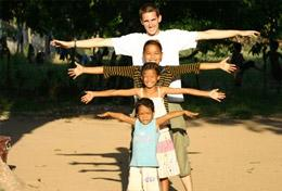 A High School Special volunteer poses in a creative way with the children from his Care & Community placement in Cambodia.