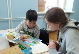 A High School Special volunteer works closely with a local child in Mongolia to improve his reading and literacy skills.