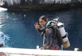 A Conservation & Community volunteer prepares for a survey dive to monitor marine life off the coast of Thailand.