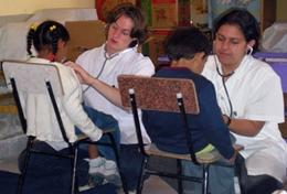 Two high school students measure children's heart rates during a volunteer Medicine outreach in Bolivia.