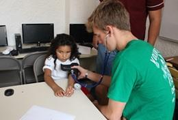 A Public Health volunteer in Mexico gains experience measuring blood pressure during his short-term high school internship.