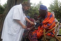 A high school student volunteering on our Public Health project in Tanzania measures a local person's blood pressure.