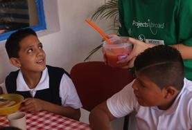 A Social Work volunteer in Mexico sits down for a meal with local children to chat to them and learn more about them during her internship.