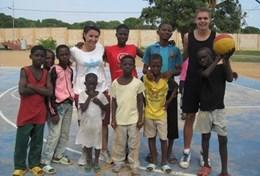 A Sports volunteer poses with a group of children after coaching them and improving their fitness at our Multi-sports placement in Ghana.
